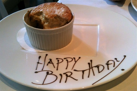 Half-eaten souffle on a plat saying Happy Birthday