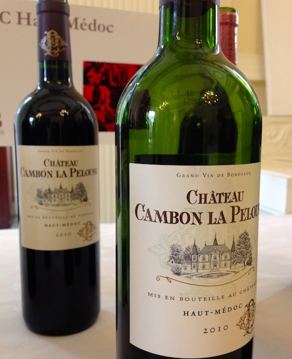 Two bottles of Château Cambon de la Pelouse 2010 in front of a Cru Bourgeois sign