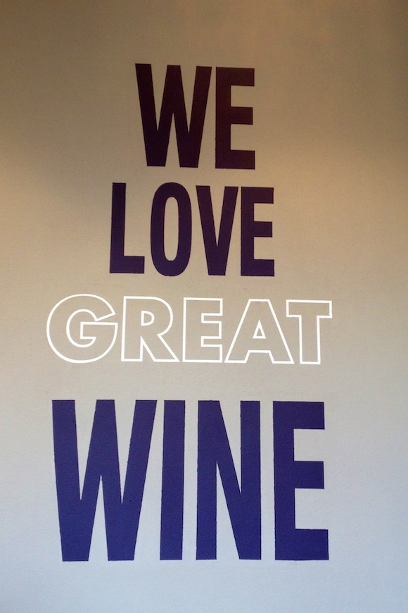 """We Love Great Wine"" sign on wall in Park + Bridge Wine Shop, Acton, London"